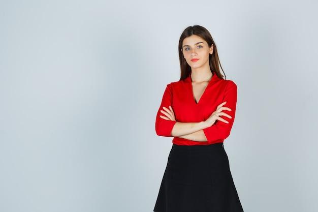 Jonge dame staande armen gekruist in rode blouse, zwarte rok en op zoek zelfverzekerd