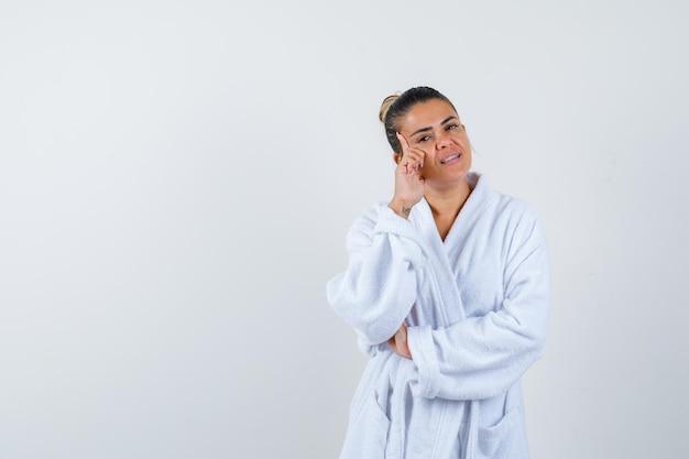 Jonge dame staat in denkende pose in badjas en ziet er attent uit