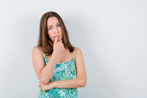 Jonge dame staat in denkende pose in blouse en kijkt peinzend, vooraanzicht.