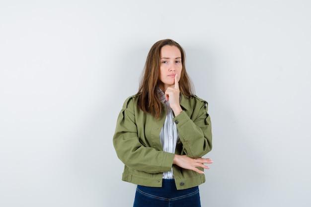 Jonge dame staat in denkende pose in shirt, jas en ziet er verstandig uit. vooraanzicht.