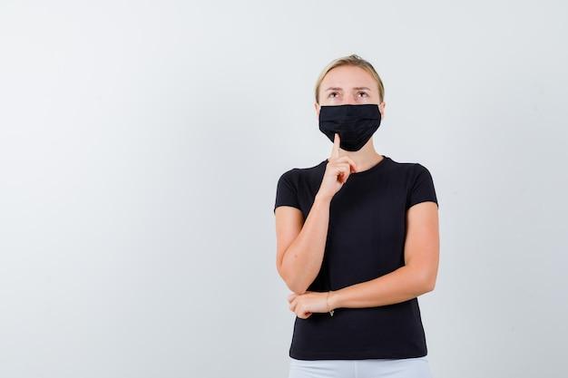 Jonge dame staat in denkende pose in t-shirt, broek, medisch masker en kijkt aarzelend