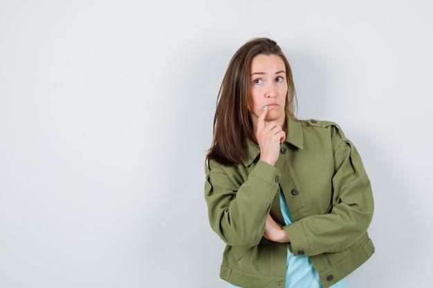 Jonge dame staat in denkende pose in t-shirt, jas en kijkt peinzend, vooraanzicht.
