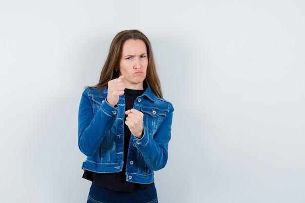 Jonge dame staat in gevecht pose in blouse, jas en ziet er zelfverzekerd uit, vooraanzicht.