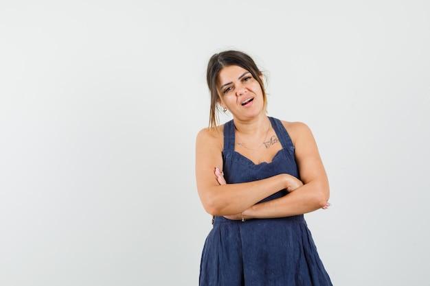 Jonge dame staat met gekruiste armen in jurk en kijkt ontevredenheid