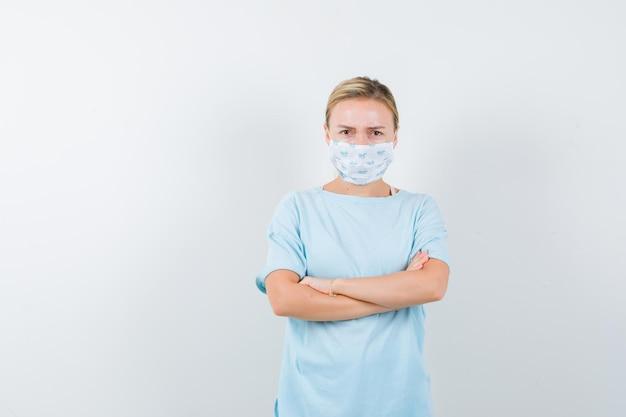 Jonge dame staat met gekruiste armen in t-shirt, masker en kijkt boos