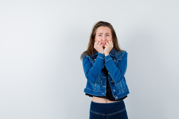 Jonge dame steunt kin op handen in blouse, jas, spijkerbroek en ziet er depressief uit, vooraanzicht.