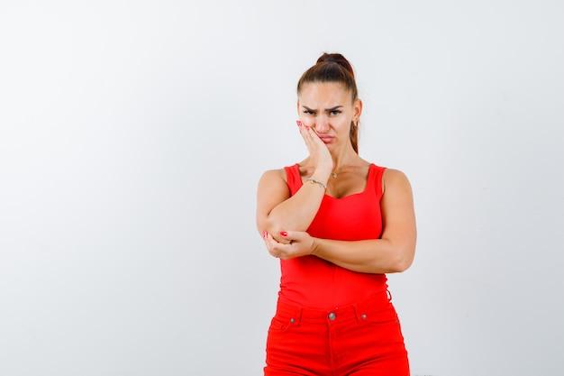 Jonge dame steunt wang bij de hand in een rood hemd, rode broek en kijkt wrokkig. vooraanzicht.