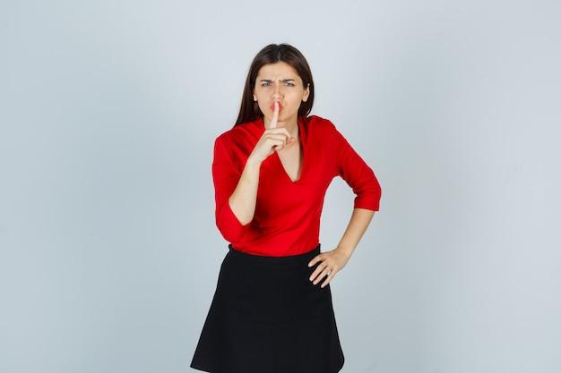 Jonge dame stilte gebaar in rode blouse, zwarte rok tonen en boos kijken