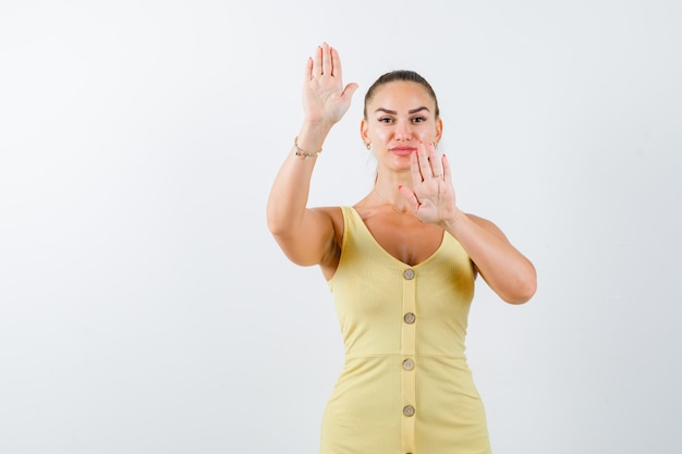 Jonge dame stop gebaar in gele jurk tonen en op zoek zelfverzekerd. vooraanzicht.