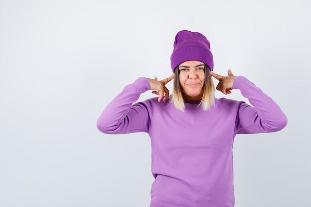 Jonge dame stopt oren met vingers in paarse trui, muts en ziet er tevreden uit, vooraanzicht.