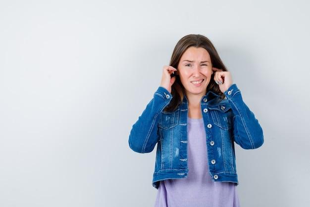 Jonge dame stopt oren met vingers in t-shirt, jas en ziet er verveeld uit. vooraanzicht.