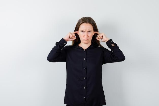 Jonge dame stopt oren met vingers terwijl ze boos kijkt
