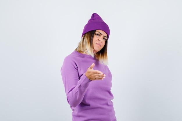 Jonge dame strekt haar handen uit naar de camera in paarse trui, muts en ziet er serieus uit. vooraanzicht.