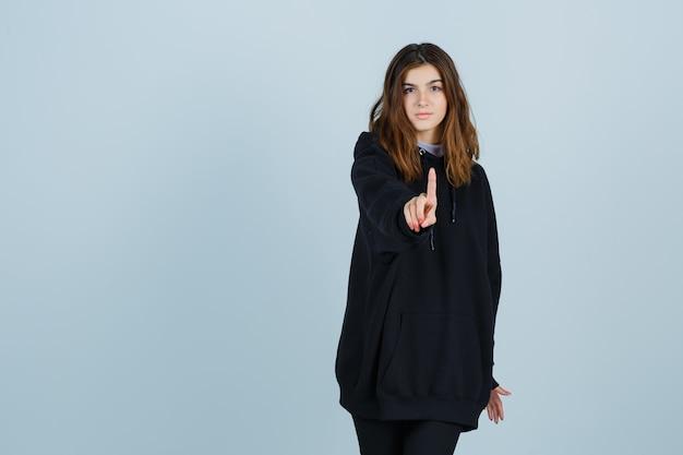 Jonge dame toont een minuut gebaar in een oversized hoodie, broek en kijkt serieus. vooraanzicht.