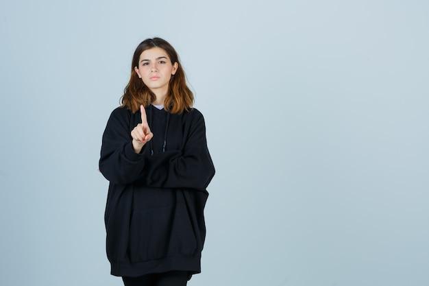 Jonge dame toont een minuut gebaar in een oversized hoodie, broek en ziet er zelfverzekerd uit, vooraanzicht.