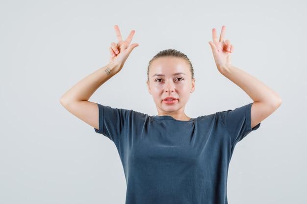 Jonge dame toont v-teken zoals hoorns in grijs t-shirt en ziet er grappig uit