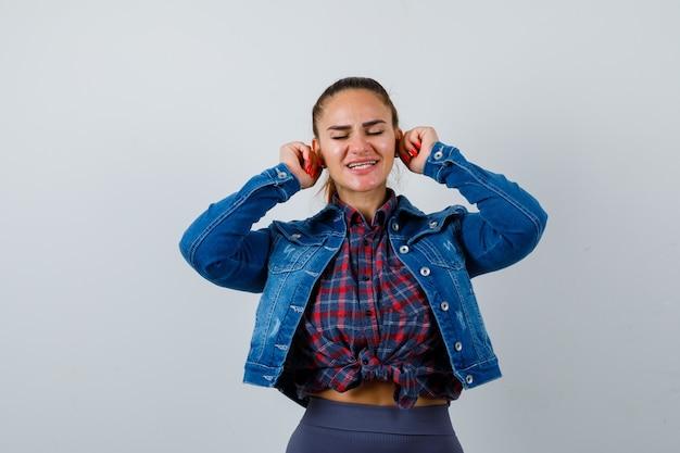 Jonge dame trekt haar oorlellen naar beneden in een geruit overhemd, een spijkerjasje en ziet er grappig uit. vooraanzicht.