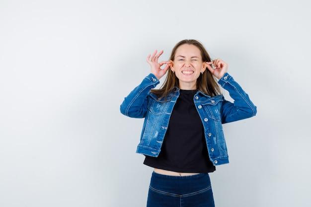 Jonge dame trekt haar oren in blouse en ziet er grappig uit.