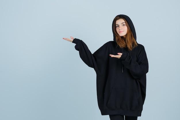 Jonge dame verwelkomt in oversized hoodie, broek en ziet er gelukkig uit. vooraanzicht.