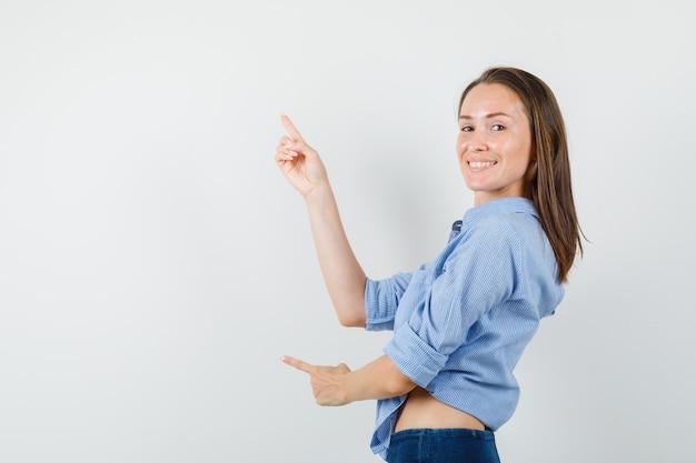 Jonge dame vingers omhoog in blauw shirt, broek en op zoek vrolijk