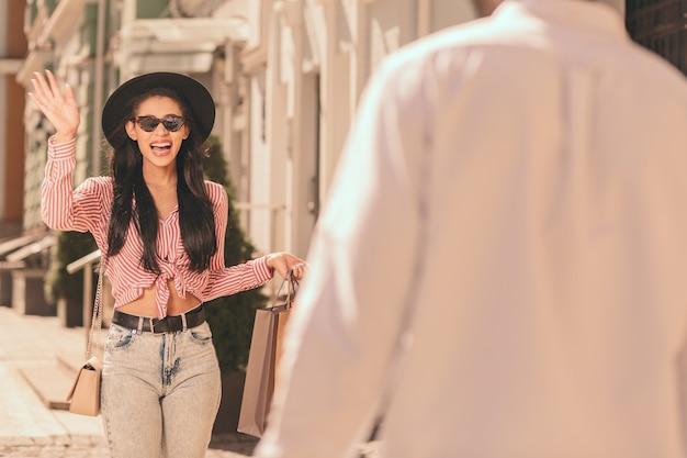 Jonge dame voelt zich opgewonden en zwaait naar een vriend op straat
