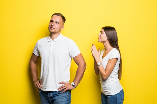 Jonge dame vraagt haar vriendje om iets te doen geïsoleerd op gele achtergrond