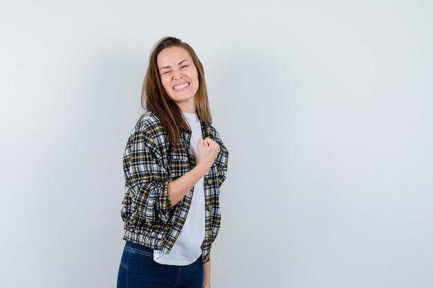 Jonge dame vuist opheffen terwijl poseren in t-shirt, jasje, spijkerbroek en op zoek zalig, vooraanzicht.