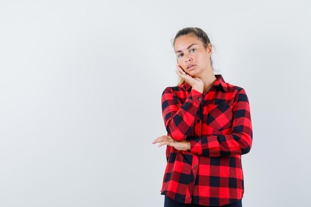 Jonge dame wang leunend op palm in geruit overhemd en ziet er schattig uit