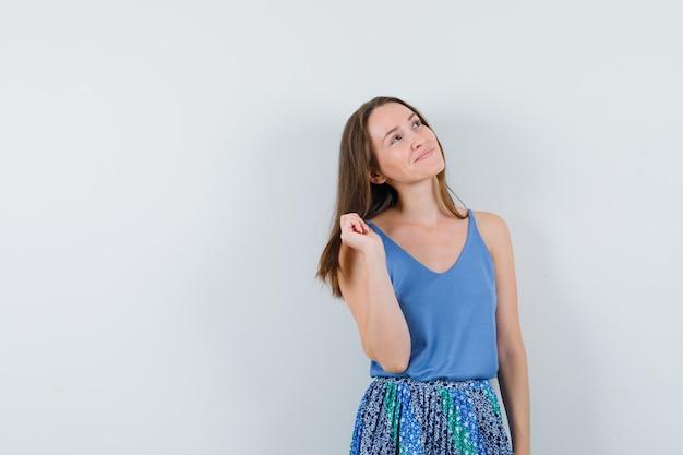 Jonge dame wegkijken in blouse, rok en enthousiast kijken. vooraanzicht. ruimte voor tekst