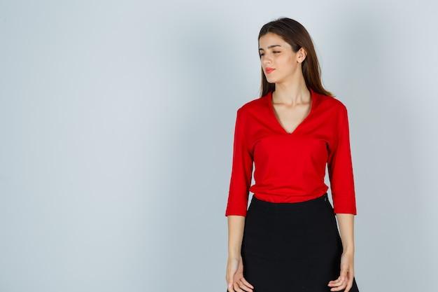 Jonge dame wegkijken in rode blouse, rok en peinzend kijken