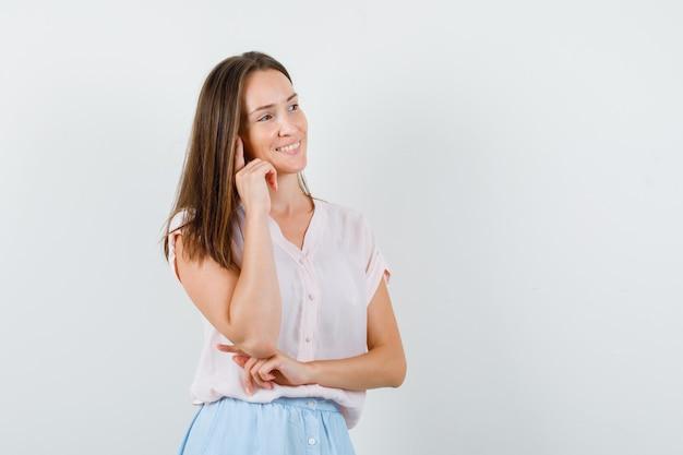 Jonge dame wegkijken terwijl ze in t-shirt, rok denkt en optimistisch kijkt. vooraanzicht.