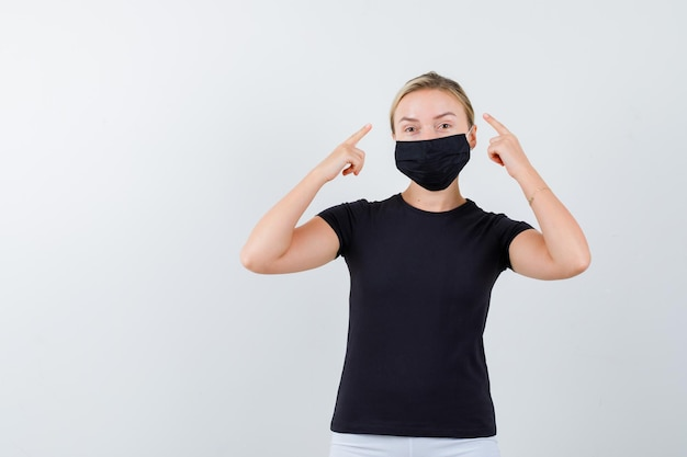 Jonge dame wijst hoofd in t-shirt, broek, medisch masker en ziet er trots uit