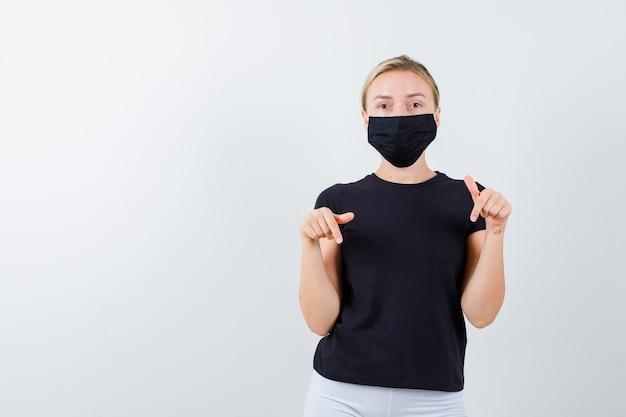 Jonge dame wijst naar beneden in t-shirt, broek, medisch masker en ziet er zelfverzekerd uit