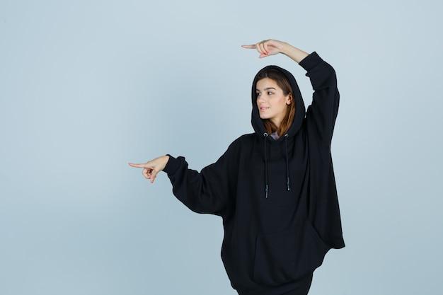 Jonge dame wijst naar de linkerkant in oversized hoodie, broek en ziet er zelfverzekerd uit. vooraanzicht.