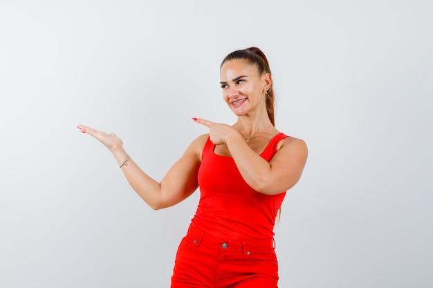 Jonge dame wijst naar de linkerkant in rood hemd, rode broek en ziet er vrolijk uit, vooraanzicht.