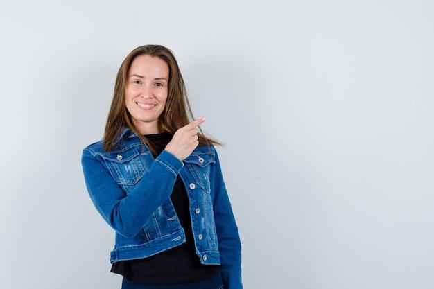 Jonge dame wijst naar de rechterbovenhoek in blouse, jas en ziet er vrolijk uit. vooraanzicht.