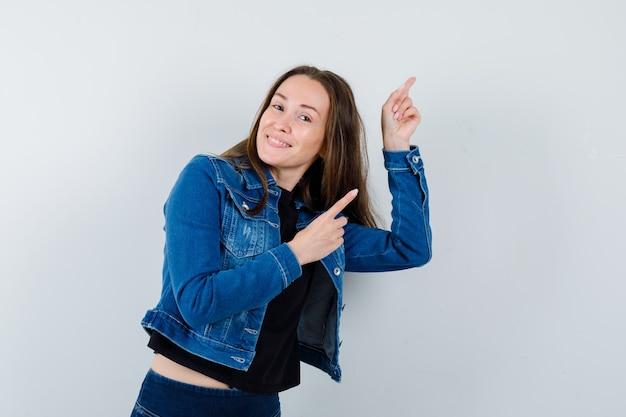 Jonge dame wijst naar de rechterbovenhoek in blouse, jas en ziet er zelfverzekerd uit, vooraanzicht.