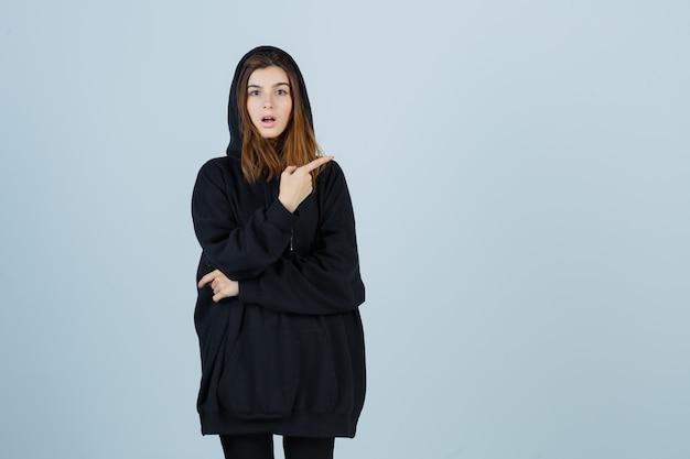 Jonge dame wijst naar de rechterkant in oversized hoodie, broek en kijkt verbaasd, vooraanzicht.