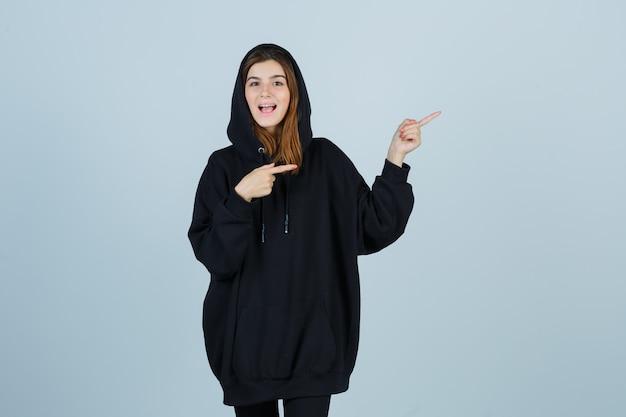 Jonge dame wijst naar de rechterkant in oversized hoodie, broek en kijkt zalig, vooraanzicht.