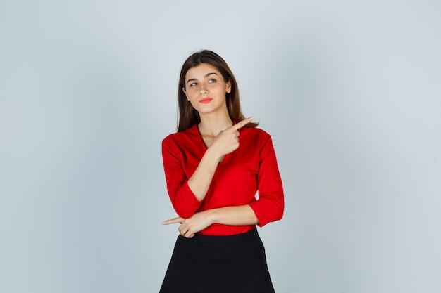 Jonge dame wijst naar de rechterkant in rode blouse, rok en ziet er schattig uit