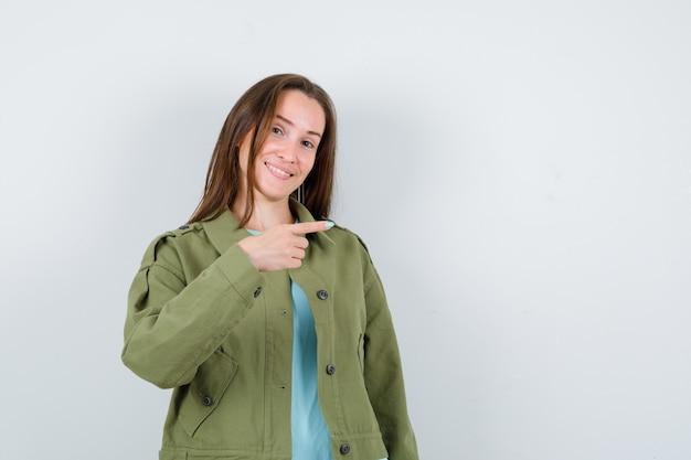Jonge dame wijst naar de rechterkant in t-shirt, jas en ziet er vrolijk uit. vooraanzicht.