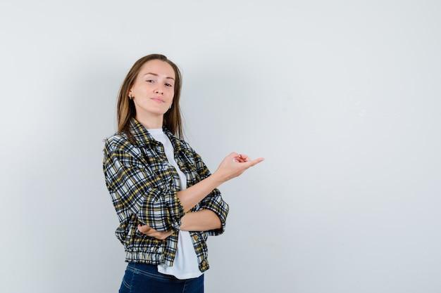 Jonge dame wijst naar de rechterkant in t-shirt, jas, spijkerbroek en ziet er zelfverzekerd uit. vooraanzicht.