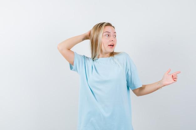 Jonge dame wijst naar de rechterkant terwijl ze de hand op het hoofd houdt in een t-shirt en verbaasd kijkt, vooraanzicht.