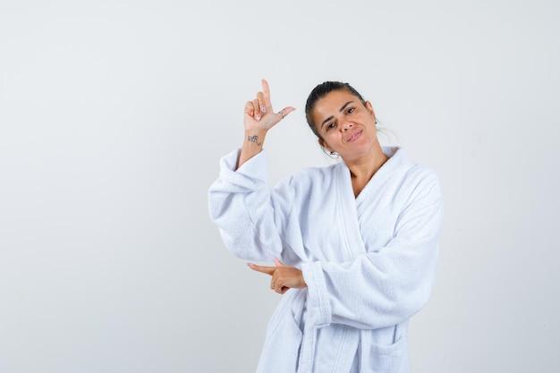 Jonge dame wijst opzij in badjas en ziet er vrolijk uit