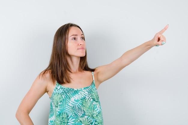 Jonge dame wijst opzij in blouse en ziet er zelfverzekerd uit, vooraanzicht.