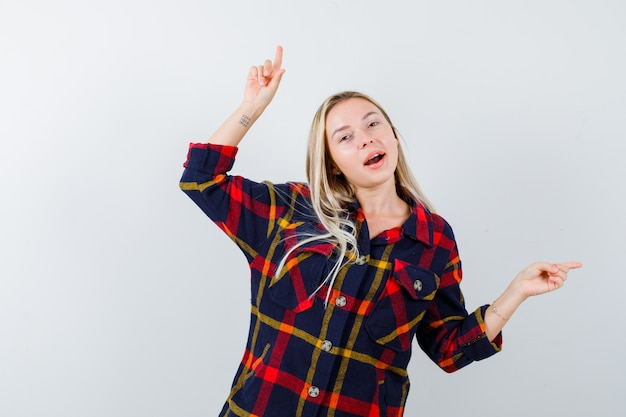 Jonge dame wijst opzij in geruit overhemd en kijkt gelukkig, vooraanzicht.