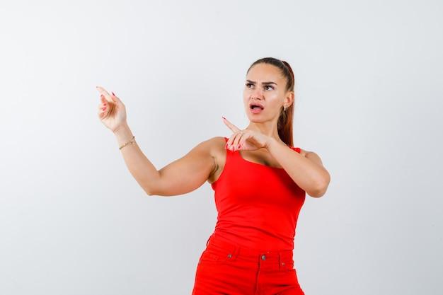 Jonge dame wijst opzij in rood hemd, rode broek en kijkt perplex, vooraanzicht.