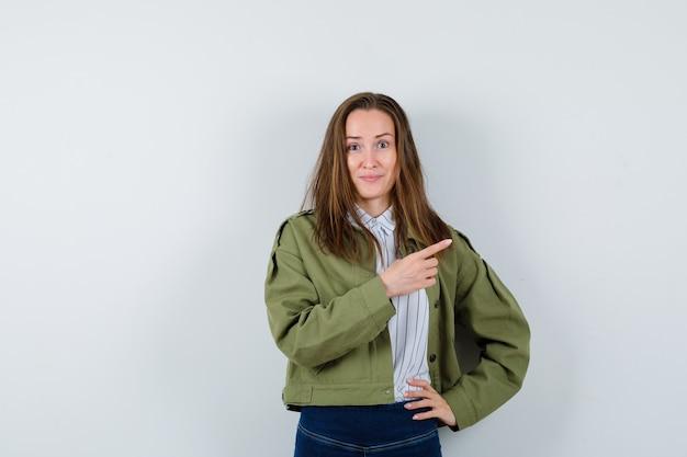 Jonge dame wijst opzij in shirt, jas en ziet er vrolijk uit, vooraanzicht.