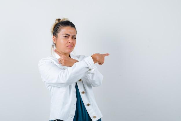 Jonge dame wijst opzij in shirt, witte jas en ziet er zelfverzekerd uit. vooraanzicht.