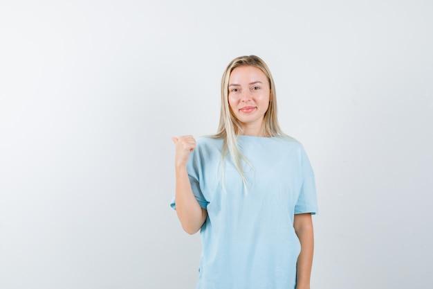 Jonge dame wijst terug met duim in t-shirt en kijkt zelfverzekerd, vooraanzicht.